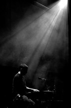 stage lights shining on a musician playing a keyboard