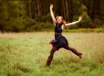 a joyful woman dancing in a field