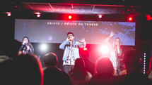 people holding microphones singing during a worship service