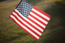 An American Flag being held up in a field