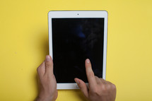 Hands holding an electronic tablet on a yellow background.