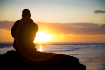 man sitting at a rock at sunset looking out at the ocean