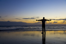 man standing on a beach with open arms