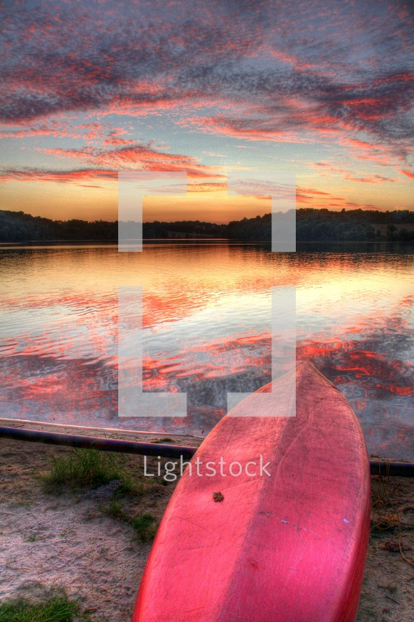 pink and purple clouds reflecting on water and a boat flipped over on a lake shore