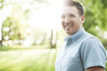 smiling man standing outdoors with natural sun flare.