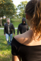 two men in hoodies approaching a woman