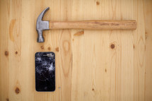 Broken iphone on a wood board with a hamper.