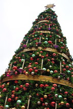 Decorated Christmas tree with gold, red, purple, ball ornaments hanging from it.