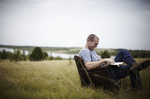 man sitting in a chair in a field reading