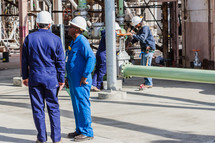 construction workers in hard hats plant pipe piping industrial steel
