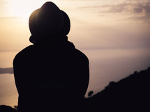 silhouette of a man in a hat looking out over an ocean sunset