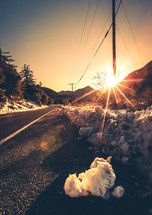snow pushed to the side of a road and a sunburst behind power poles