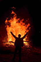 man with his hands raised in front of a burning bonfire