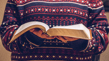 a woman reading a Bible in a sweater