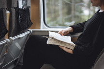 Girl reading her bible on en empty train.