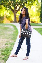 young woman with a purse standing on a sidewalk
