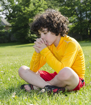 Child sitting in the grass praying.