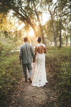 bride and groom walking along an outdoor path holding hands