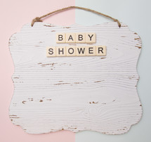 white wood sign on a pink and blue background