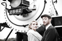 Couple, dressed in 1940's clothing, standing in front of the engine of a old train