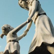 whimsical dancing mother and child statue against a blue sky