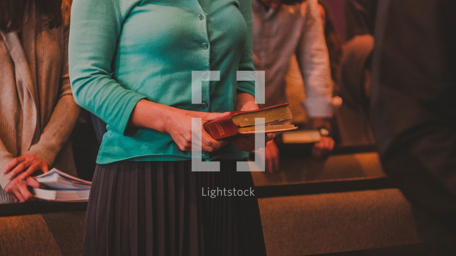 people holding hymnals at church