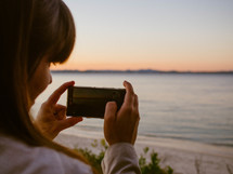 a woman taking pictures of a beach at sunset