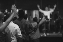 parishioners with raised hands at a worship service