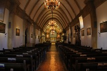 A church sanctuary with a curved ceiling and chandeliers.