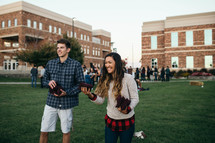 a young man and young woman tossing bean bags outdoors