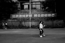 Young Chinese women walking along a road near a sign.