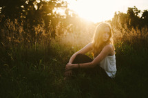 a young woman sitting in grass at sunset