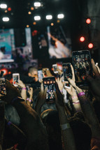 audience taking pictures with cellphones at a concert