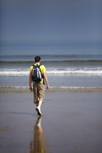 A man in a backpack walking along the beach.