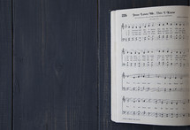 pages of an open hymnal - Jesus Loves me this I know