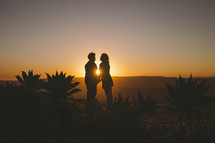 silhouette of a couple holding hands at sunset in a desert