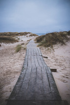 A board walk leading through sand dunes to the sea.