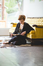 a woman sitting on the floor reading