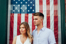 a couple standing in front of an American flag