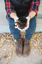 a woman sitting on a curb holding a mug of tea