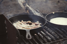 cooking bacon and eggs on skillets