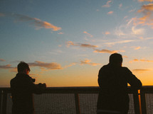 silhouettes of men looking over a railing at sunset
