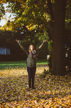 a woman standing in fall leaves with open arms