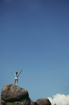 woman standing on top of a rock with her hands raised in worship to God