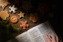 a woman reading a Bible and baking gingerbread Christmas cookies