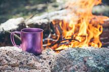 a coffee mug next to a camp fire