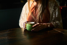 a woman in a sweater with a coffee mug