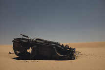 burned out overturned car in a desert