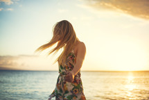 a blonde woman walking on a beach at sunset