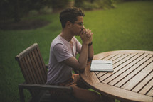 a young man reading a Bible in his backyard and praying